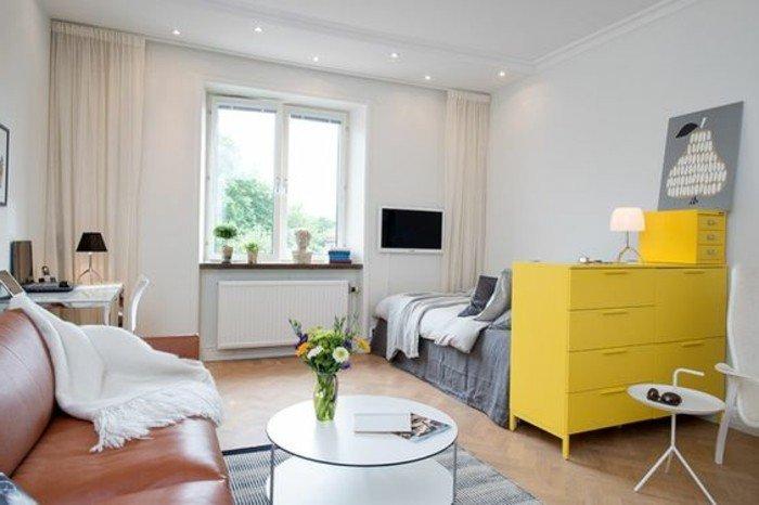 gelbe Regale, ein Ledersofa, ein runder Tisch, ein grauer Teppich, Einrichtungsideen Wohnzimmer