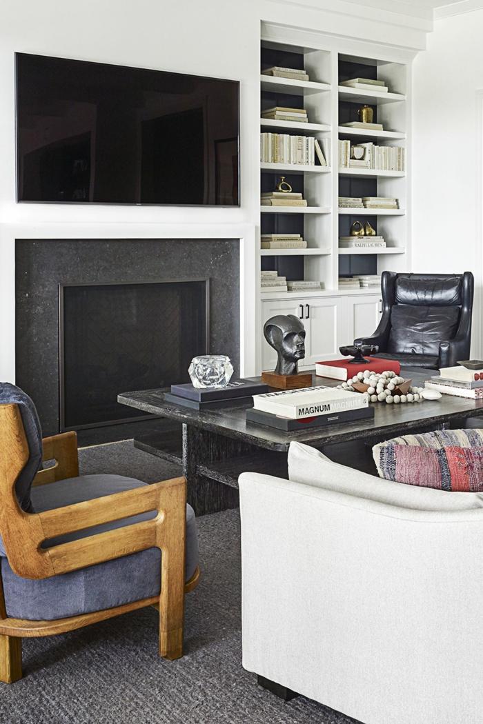 ein Tisch in schwarzer Farbe, eine Fernseh- und Kaminwand, ein grauer Teppich, eine weißes Regal, Wohnzimmerwand