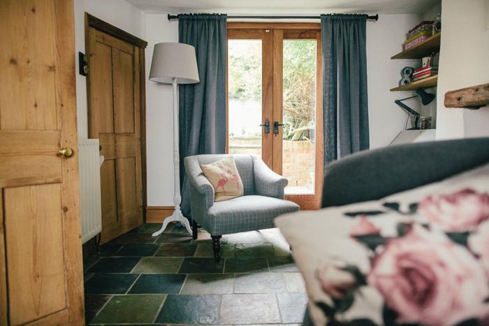 ein grauer Sessel, bunte Fliesen, Türen aus Holz, blauer Vorhang, weiße Wände, Wohnzimmerwand