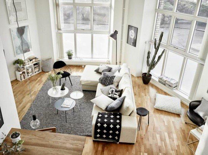 weißes Sofa mit schwarz weißen Kissen, drei runde Tischen, ein grauer Teppich, Einrichtungsideen Wohnzimmer