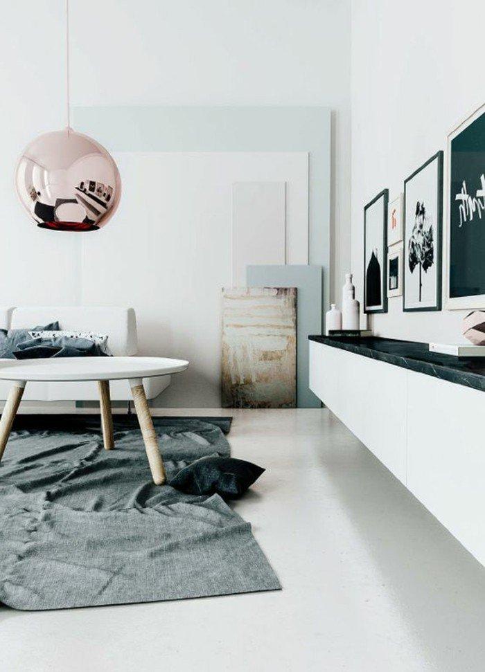 ein grauer Teppich, ein niedriger weißer Tisch, eine Pendellampe, verschiedene Bilder in Schwarz Weiß