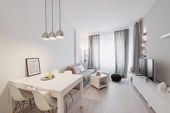 ein graues Sofa, ein weißes Regal, ein kleiner Tisch, schwarzer Hocker, Einrichtungsideen Wohnzimmer