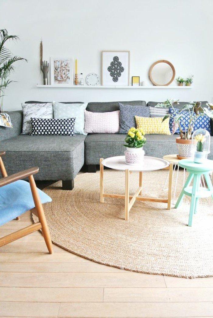 eine weiße Leistne mit vielen Bildern, viele kleine Tische, ein runder Teppich, Einrichtungsideen Wohnzimmer