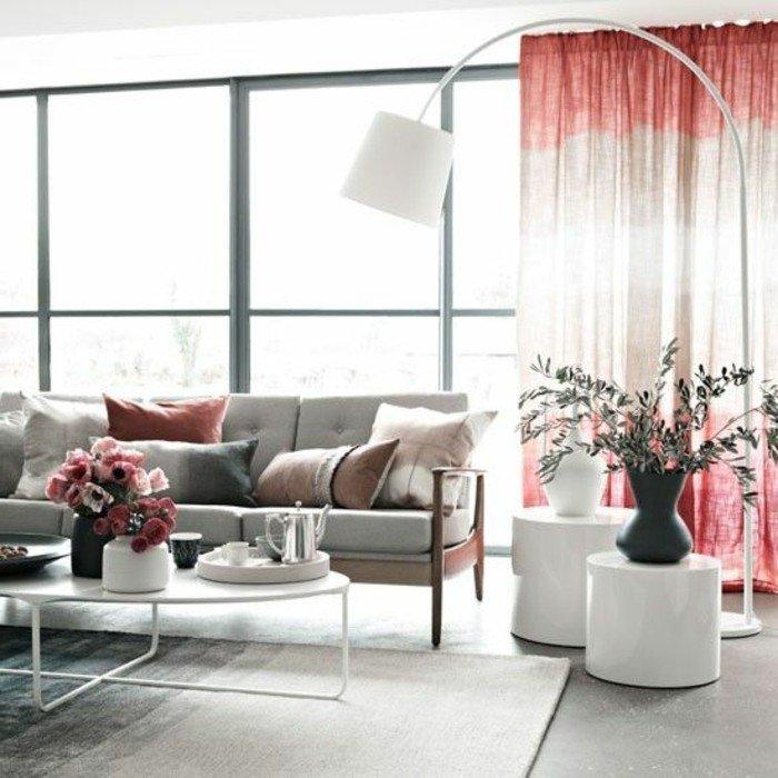 ein graues Sofa, bunte Kissen, ein Vorhang in zwei Farben, ein grauer Teppich, zwei Vasen, Einrichtungsideen Wohnzimmer