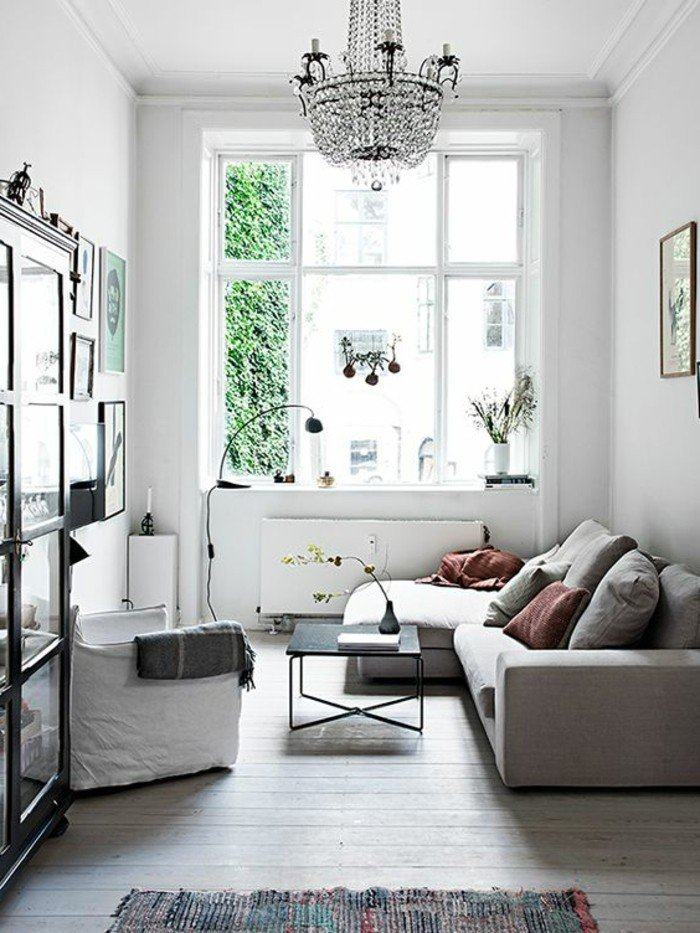 weiße Wandfarbe, graue Eckcouch, ein niedriger Tisch, Diele, ein schwarzes Regal, Einrichtungsideen Wohnzimmer