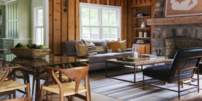 ein grauer Teppich, graues Sofa, schwarzer Sessel, orange Wohnzimmer Farben, ein Kamin mit Steinen