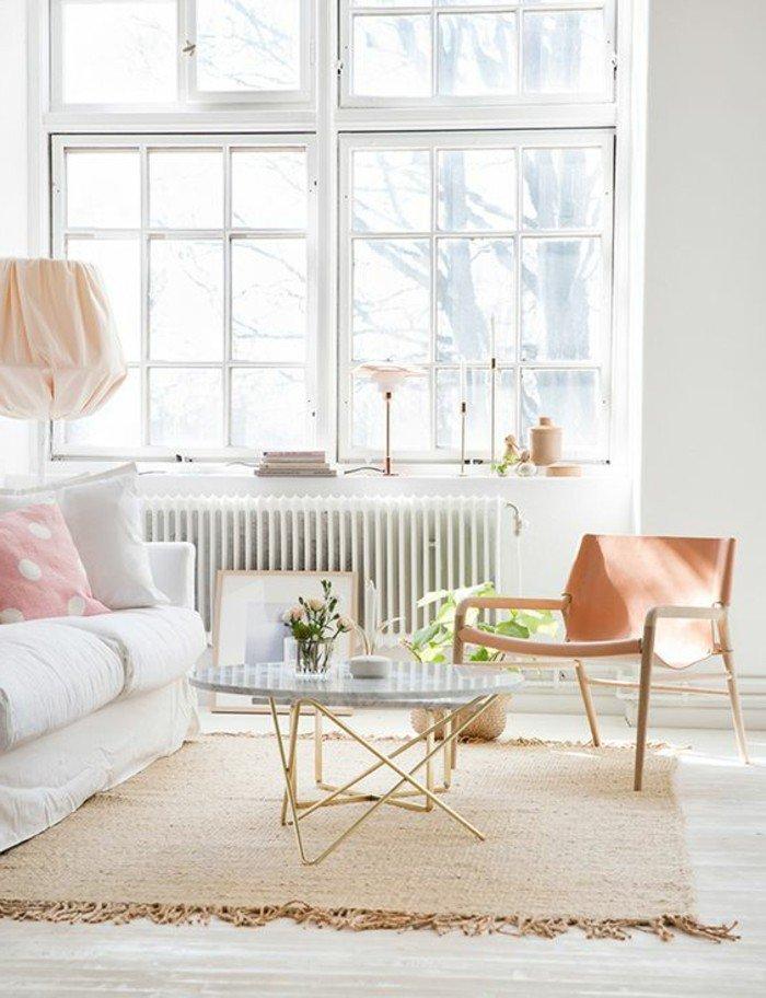 ein weißes Sofa, ein rosa Teppich, ein kleiner runder Tisch, eine Heizung, große Fenster, Einrichtungsideen Wohnzimmer