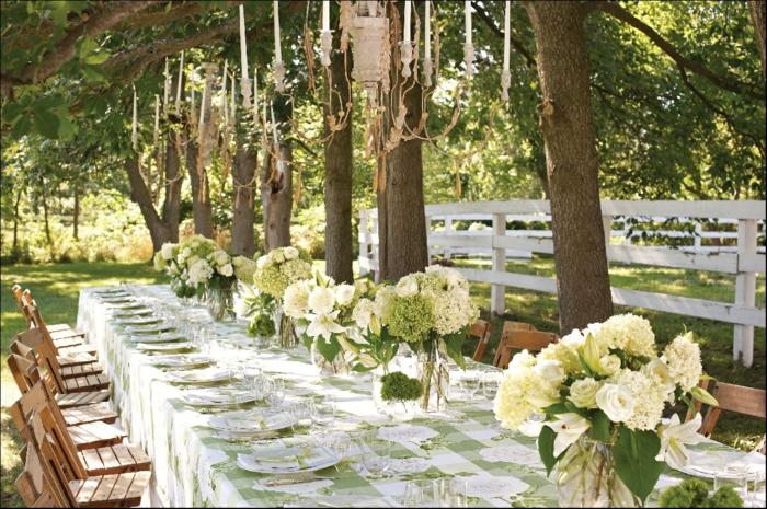 Kerzen, Blumen Tischdeko in Glas, eine Reihe von Vasen mit weißen Blumen, weiße Tischdecke