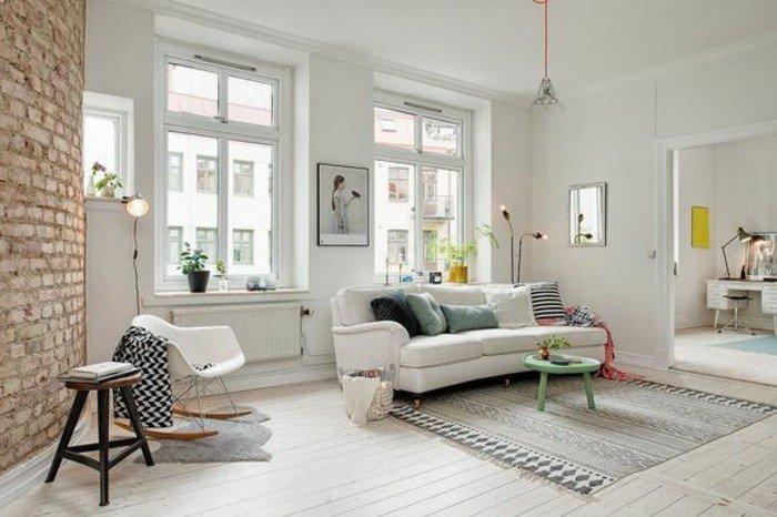 ein weißes Sofa, ein grauer Teppich, ein kleiner grünen runden Tisch, Wohnzimmer gestalten