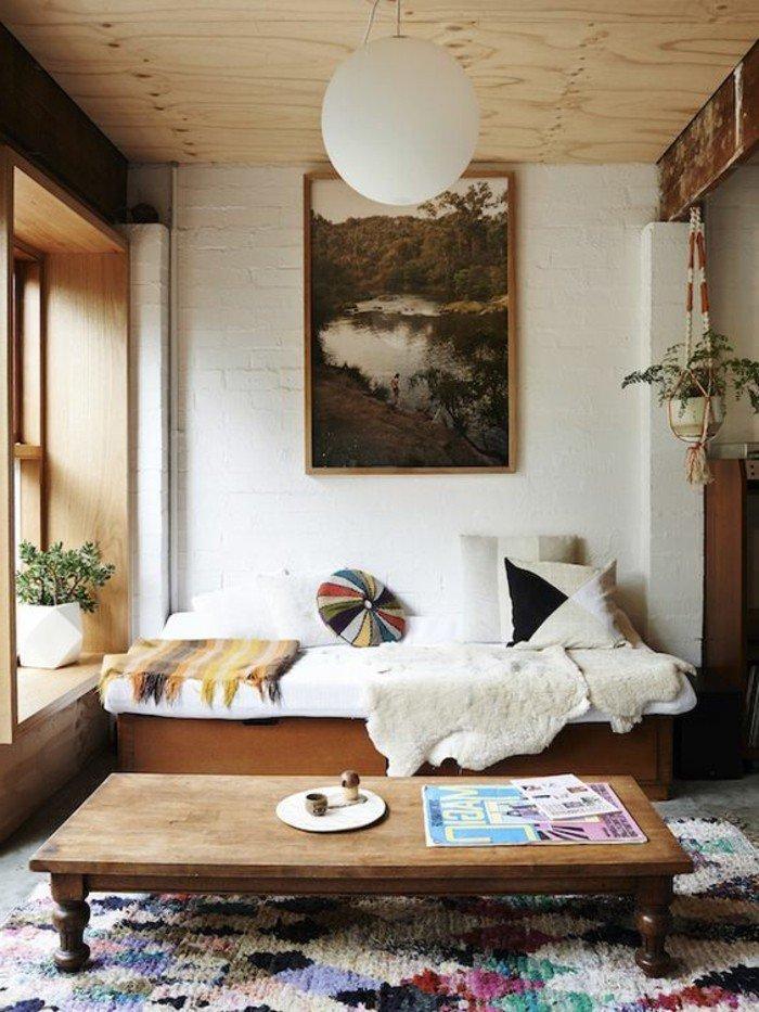 ein weißes Sofa, ein hölzerner Tisch, bunte Kissen, eine runde Lampe, ein bunter Teppich, Wohnzimmer gestalten