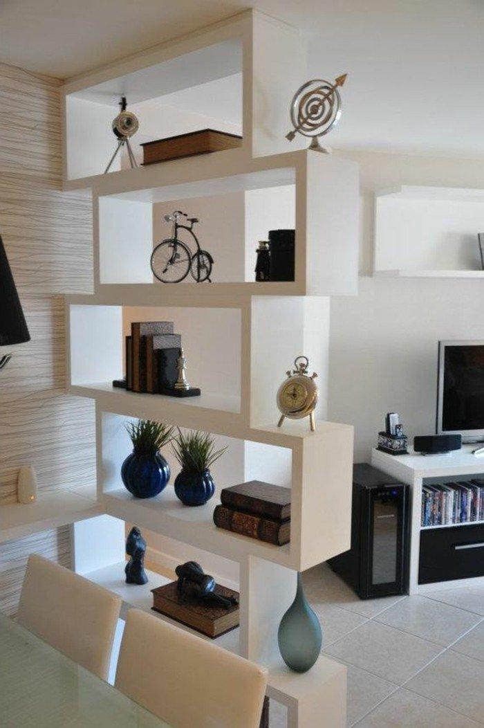 ein weißer Raumteiler mit Büchern und kleine Dekorationen, weiße Fliesen, kleine Räume einrichten