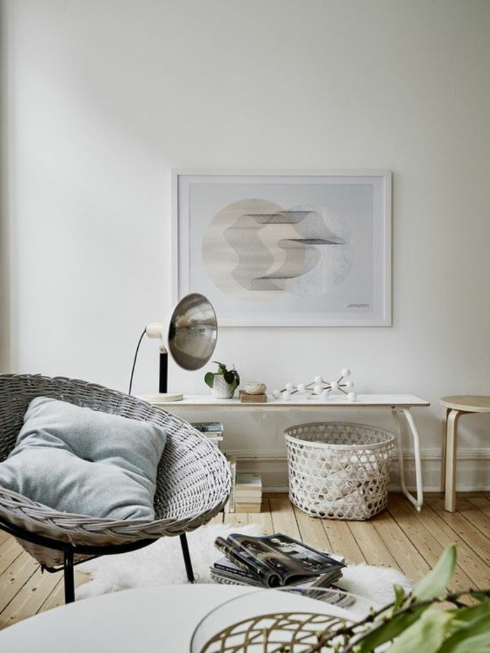 ein grauer Sessel, weiße Wände mit einem Bild, viele kleine Tische, Wohnzimmer gestalten