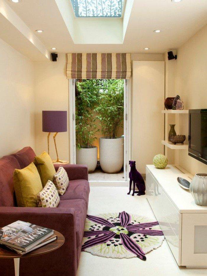 ein lila Sofa, symmetrisch gelegte Kissen, ein runder Teppich wie eine lila Blume, Wohnzimmer gestalten