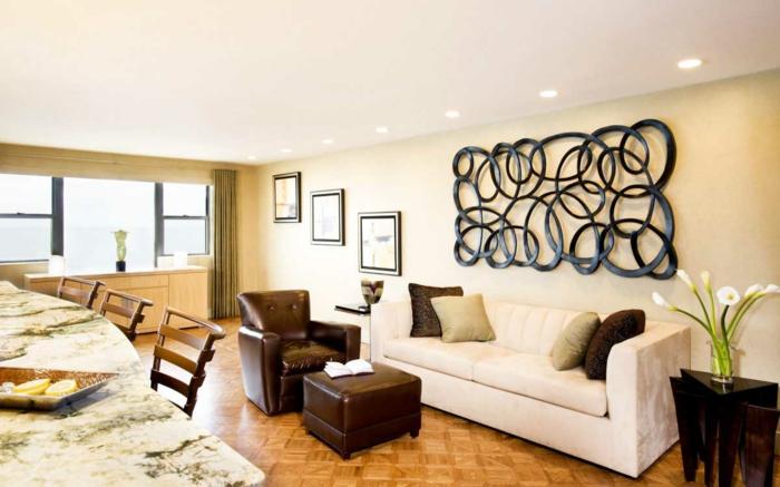 ein weißes Sofa, ein Wandbild in schwarzer Farbe mit gerundeten Motiven, Parkett Boden