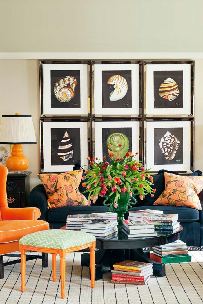 sechs Bilder, ein dunkelblaue Sofa, ein oranger Sessel, eine Vase mit Blumen, kleine Fliesen als Bodenbelag, Wohnzimmer Farben