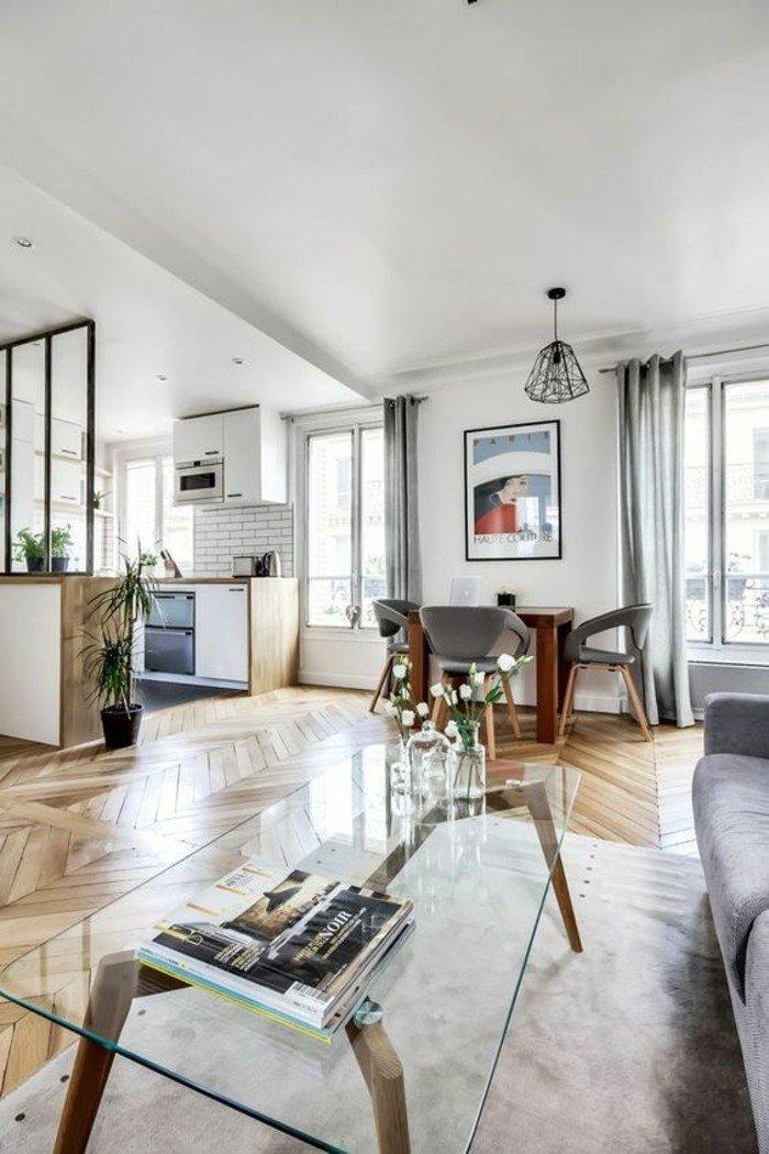 ein Tisch aus Glas, ein grauer Teppich, Parkett Boden, ein buntes Bild, weiße Wandfarbe, Wohnzimmer gestalten