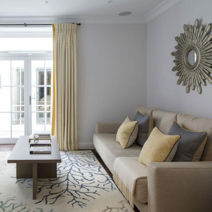 ein braunes Sofa, ein weißer Teppich mit schönen Motiven, gelbe und blaue Kissen, Wohnzimmer Farben