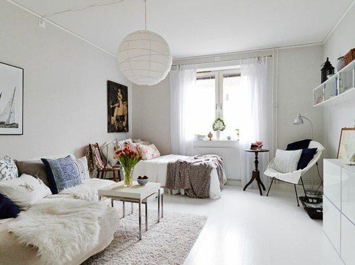 ein beiges Sofa mit weißen Decken, bunte Kissen, ein kleiner weißer Tisch, Wohnzimmer gestalten