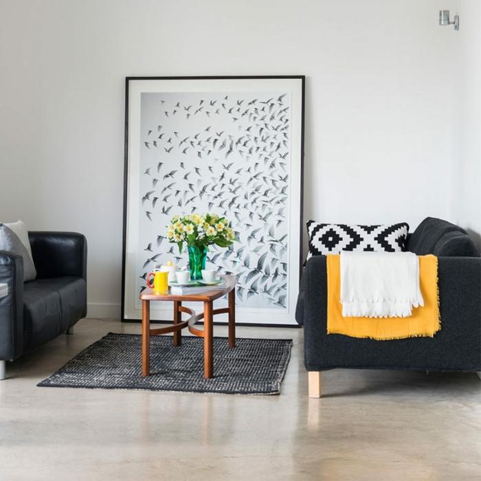 ein weißes Wandbild mit schwarzen Vögeln, zwei Sessel, ein schwarzer Teppich, ein kleiner Tisch, Wohnzimmer Ideen Wandgestaltung