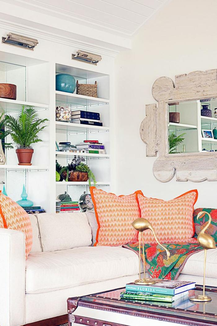 Wohnzimmer Ideen Wandgestaltung, drei rote Kissen, ein lila Tisch, eine Menge weiße Regale
