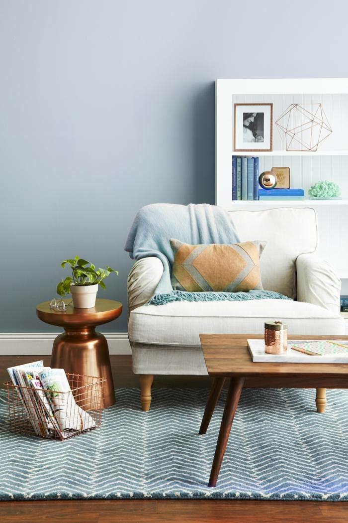 ein blauer Teppich, ein weißer Sessel, weiße Regale mit Dekorationen, ein runder Tisch, Wohnzimmer Ideen Wandgestaltung