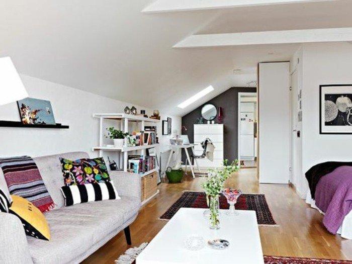 ein lila Sofa, bunte Kissen, ein weißer Tisch, Wohnzimmer gestalten, Einzimmer Dachwohnung