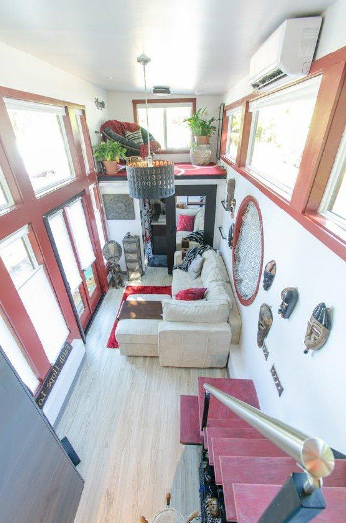 ein weißes Sofa, roter Teppich, ein Spiegel, eine Pendellampe, rote Treppen, Laminat Boden,