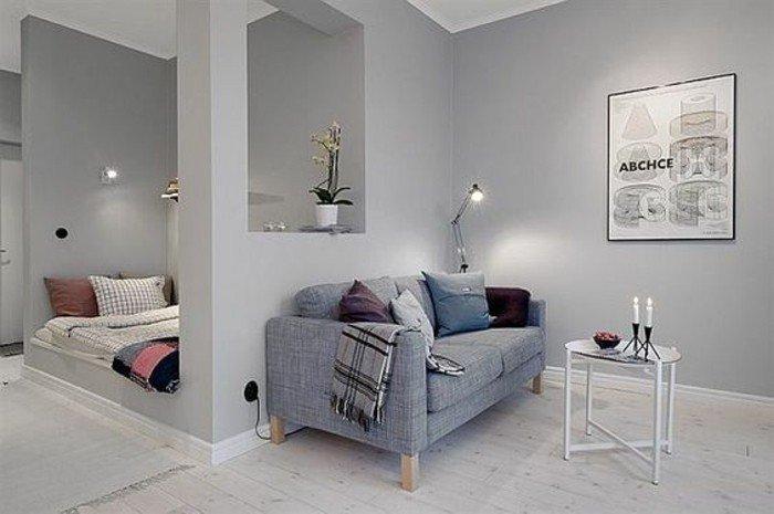 ein graues Sofa, bunte Kissen, ein schwarz-weißer Schal, ein runder weißer Tisch, kleine Räume einrichten