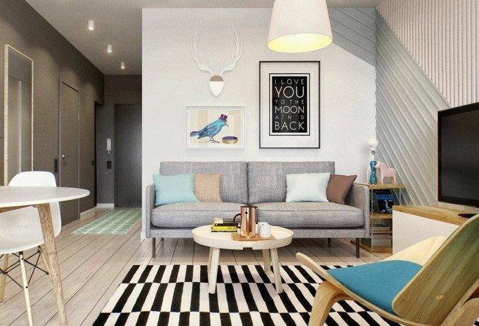 ein graues Sofa, ein Zebra Teppich, ein weißer runder Tisch, viele schöne Bilder, kleines Wohnzimmer gestalten