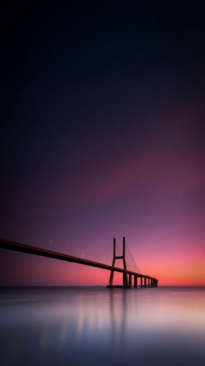 eine lange Brücke beim Sonnenaufgang, der im Wasser widerspiegelt, coole Hintergrundbilder