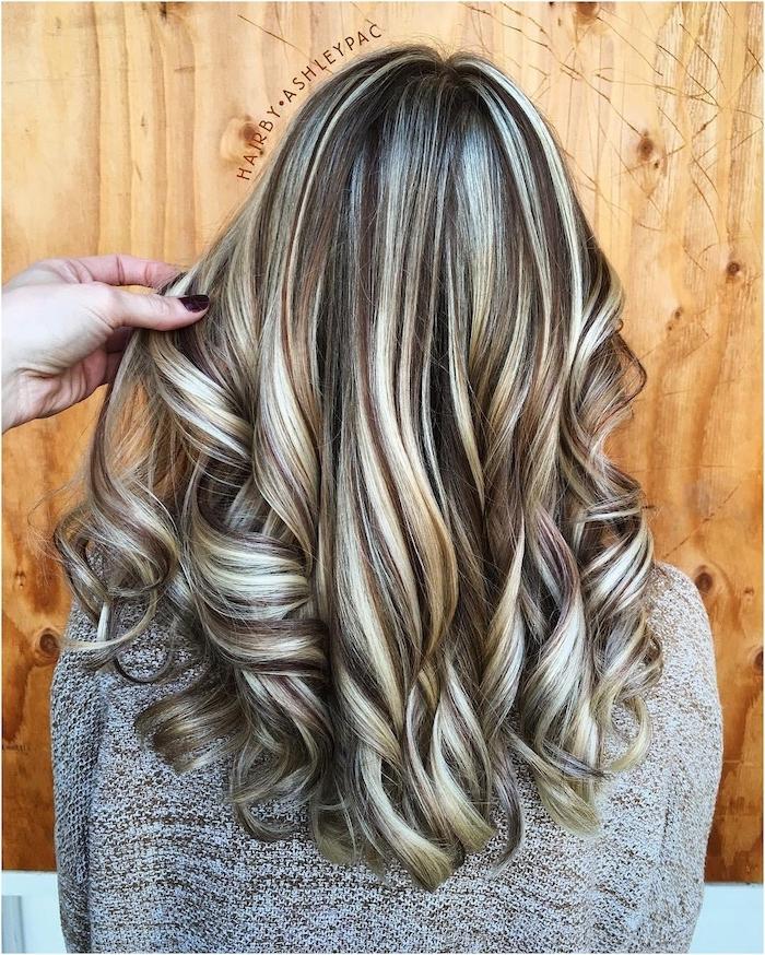 wand aus holz und eine damen frisur, strähnchen selber machen, junge frau mit haare mit langen blonden strähnchen