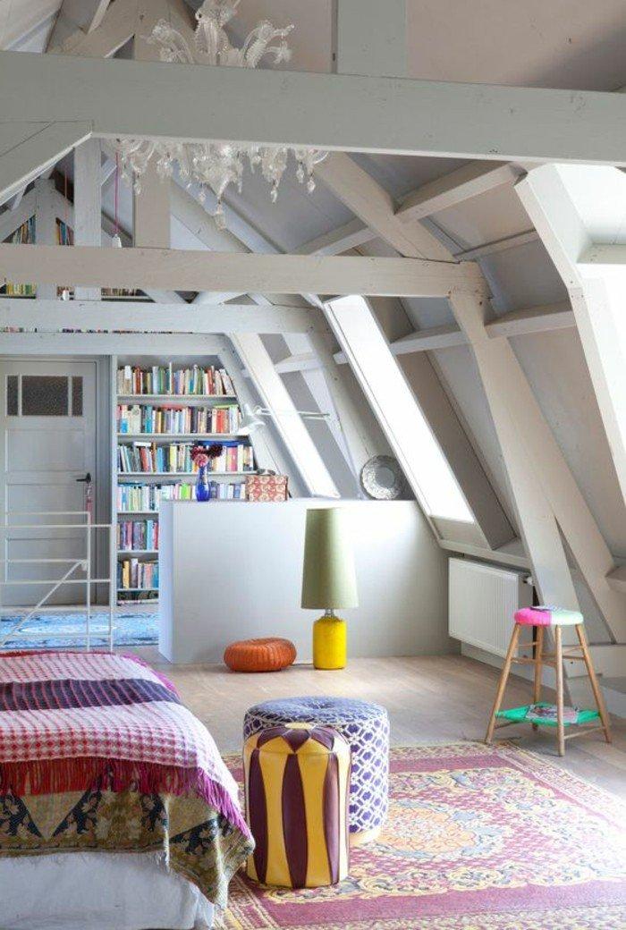ein weißes Regal mit vielen Büchern, bunter Teppich, bunte Hocker, eine Dachgeschöss, kleines Wohnzimmer einrichten