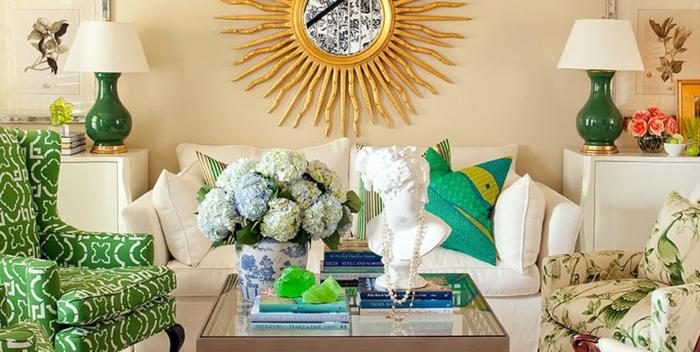 ein weißes Sofa, zwei grüne Sessel, eine Wanduhr wie die Sonne an der Wohnzimmerwand