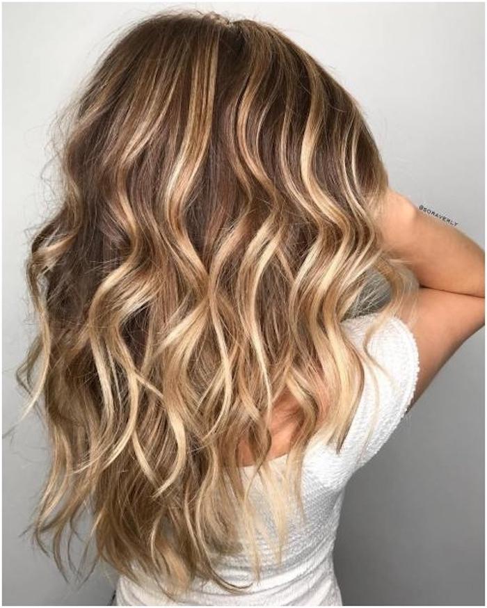 frau mit haare mit langen blonden strähnchen, ideen für damen frisuren, eine weiße wand und frau mit weißen pullover