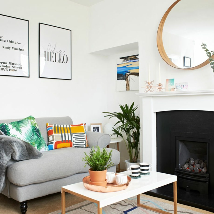 weiße Wandbilder, graues Sessel, bunte Kissen, ein weißer Tisch, ein runder Spiegel, ein schwarzer Kamin, Wohnzimmerwand