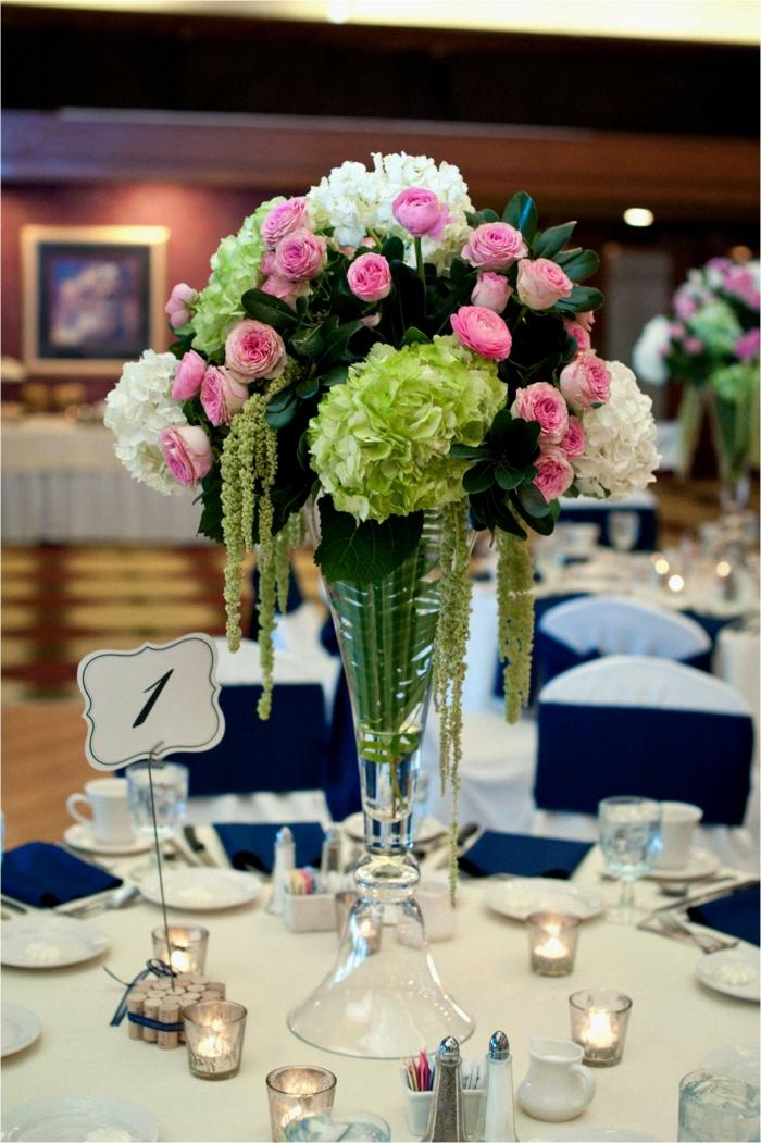 eine Vase aus Glas, rosa und weiße Blumen, weiße Tischdecke, kleine Windlichter mit Teelichter
