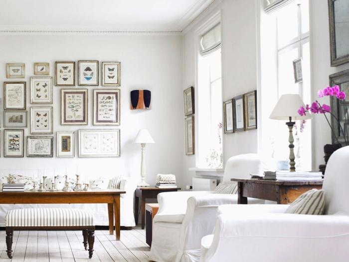 eine Menge Wandbilder, ein Tischlein aus Holz, zwei Sessel, weiße Diele, Wohnzimmerwand