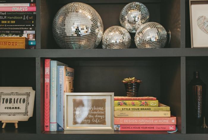 silberne Kugeln, graue Regale, bunte Bücher, Wohnzimmerwand mit einer schönen Wanddeko