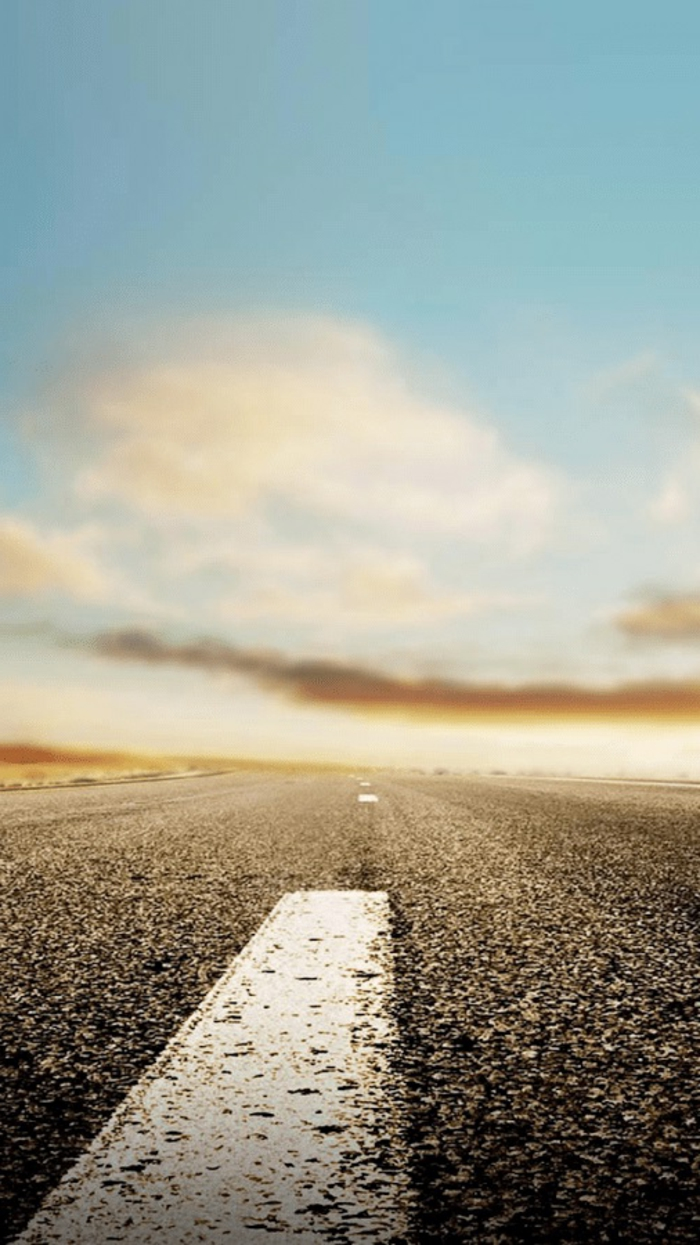 eine Landstraße mit Zeichen, in der Ferne sieht man die Sonne, rote Wolken, coole Hintergrundbilder