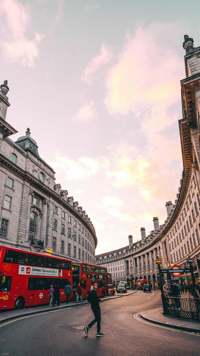 eine Straße, die gekrümmelt ist, viele hohe Gebäude darum, ein roter Buss, rosa Wolken, coole Hintergrundbilder