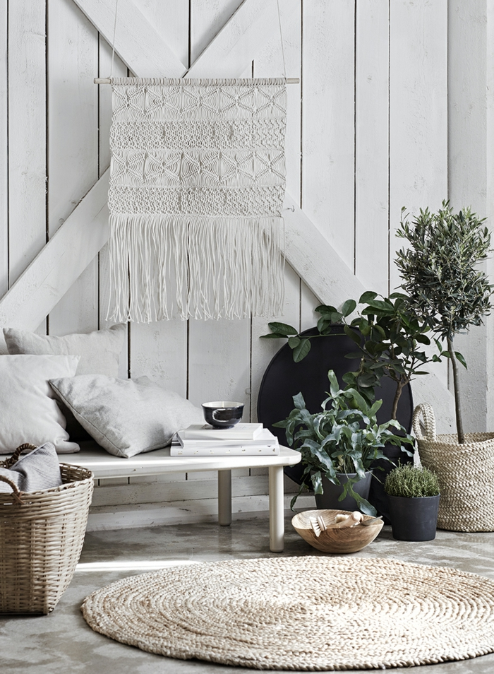 weißes Wandbild, eine weiße Wand, grüne Pflanzen, ein runder weißer Teppich, Wohnzimmerwand