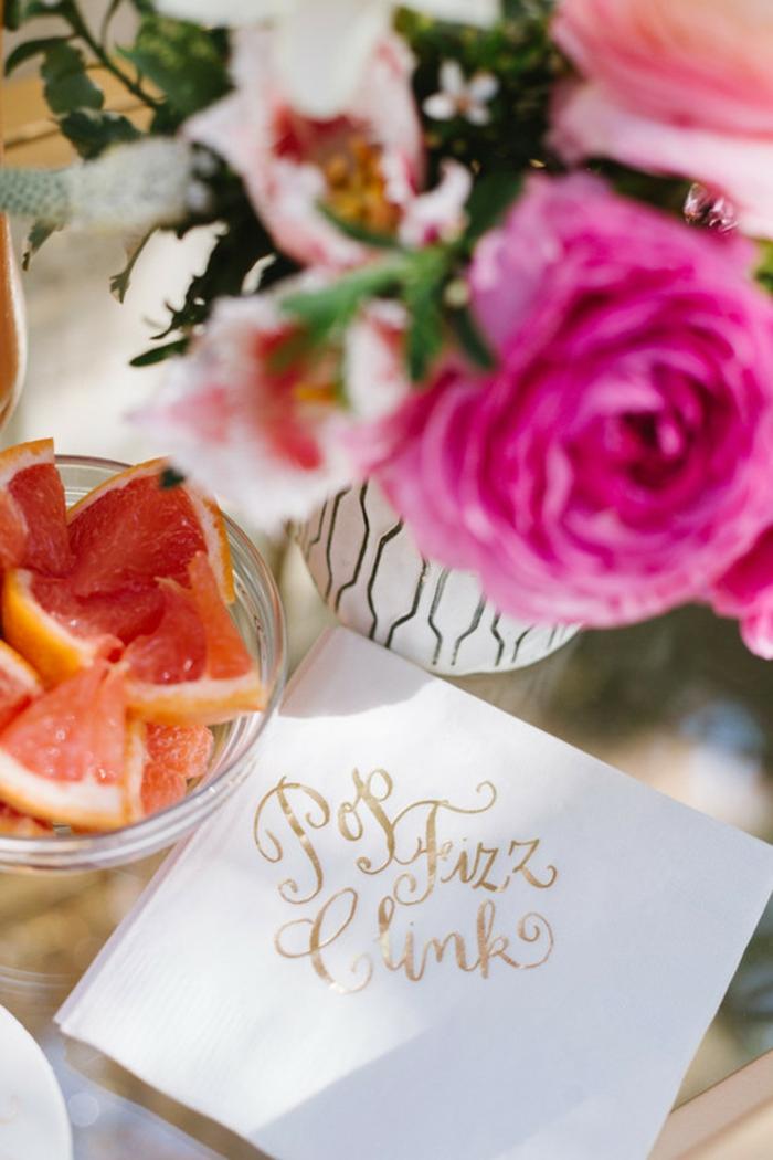 eine weiße Vase mit rosa Rosen, Grapefruit in einer gläserne Schale, eine Karte mit goldenen Schrift, Blumen Tischdeko aus Glas
