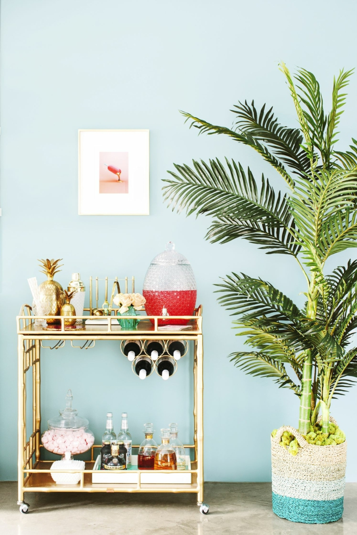 Wohnzimmerwand in blauer Farbe, ein grauer Boden, eine Zimmerpflanze, eine Karre mit Getränken