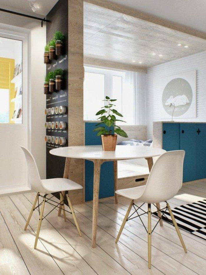 kleine wohnung selber ausstatten, runder tisch mit zwei stühlen, bett dahinten, schwarz weißer teppich