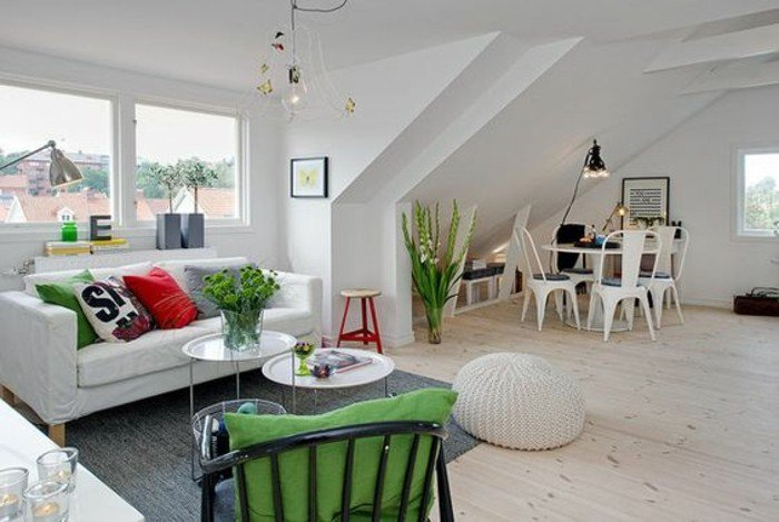 ein weißes Sofa, bunte Kissen, ein runder weißer Tisch, ein grauer Teppich, ein weißer Hocker, kleine Räume einrichten