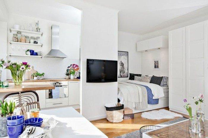 ein Laminatboden, ein weißer Tisch, ein eingebautes Bett, eine kleine Küche, kleine Räume einrichten