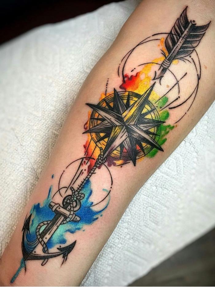 farbiges kompass tattoo am unterarm in kombination mit anker und pfeil, bunte farben