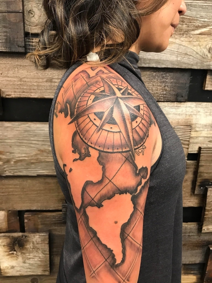 frau mit weltkarte tattoo am oberarm, lockige haare, kompass und erdteile