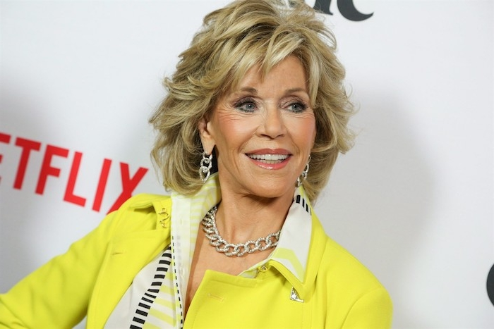 Jane Fonda Haarstyle, Stufenschnitt mit Pony, schwarze Mascara und Lipgloss, silberner Schmuck, gelber Blazer