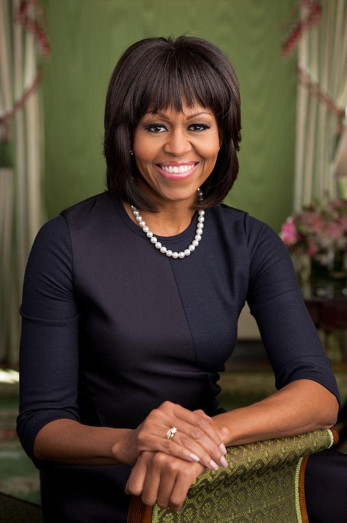 Michelle Obama Hairstyle, Stufenschnitt mit geradem Pony, glatte schwarze Haare, schwarzes Kleid und Perlenkette